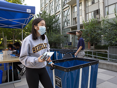 student moving into resident hall unit wearing mask